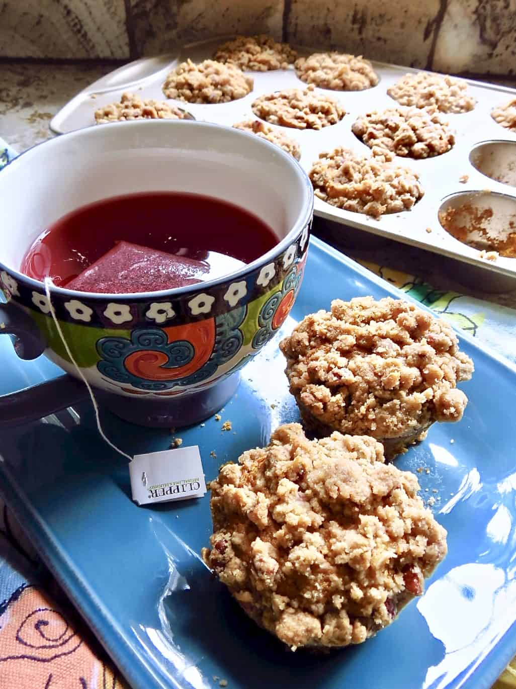 Two Pumpkin Muffins With Streusel on a blue plate with a multi-colored cup.