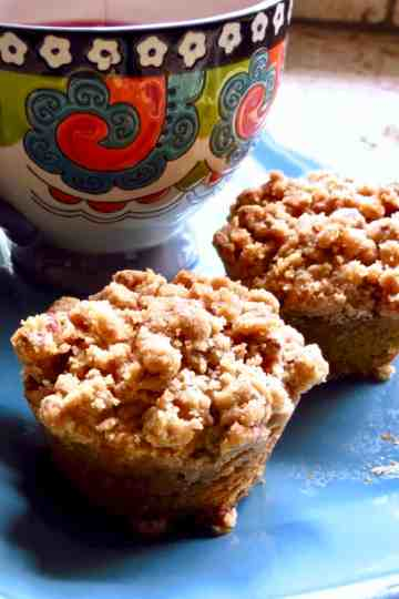 Two Pumpkin Streusel Muffins on a blue plate with a multi-colored cup.