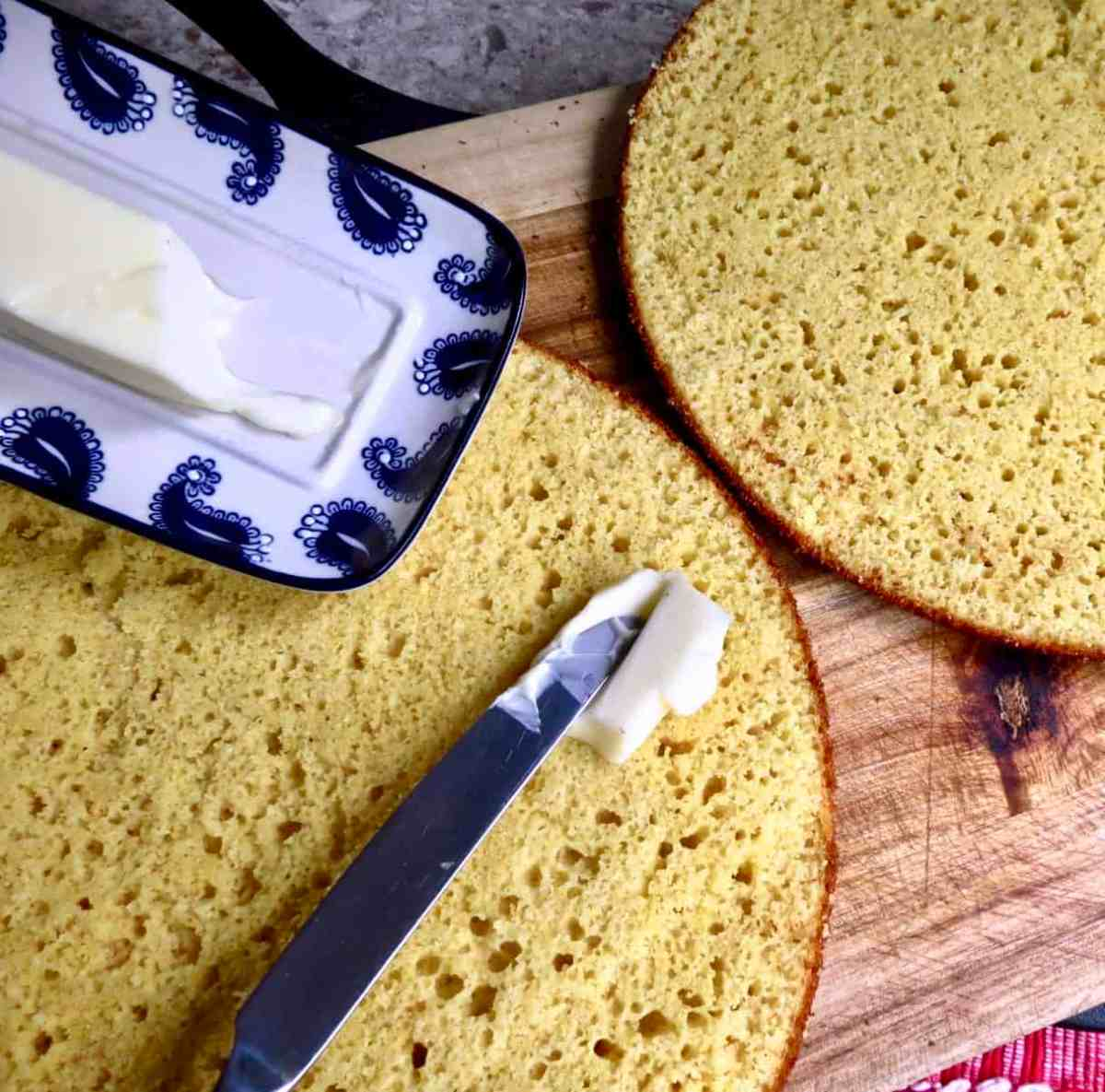 Iron Skillet Cornbread Sliced in half with butter being slathered on it near butter dish.
