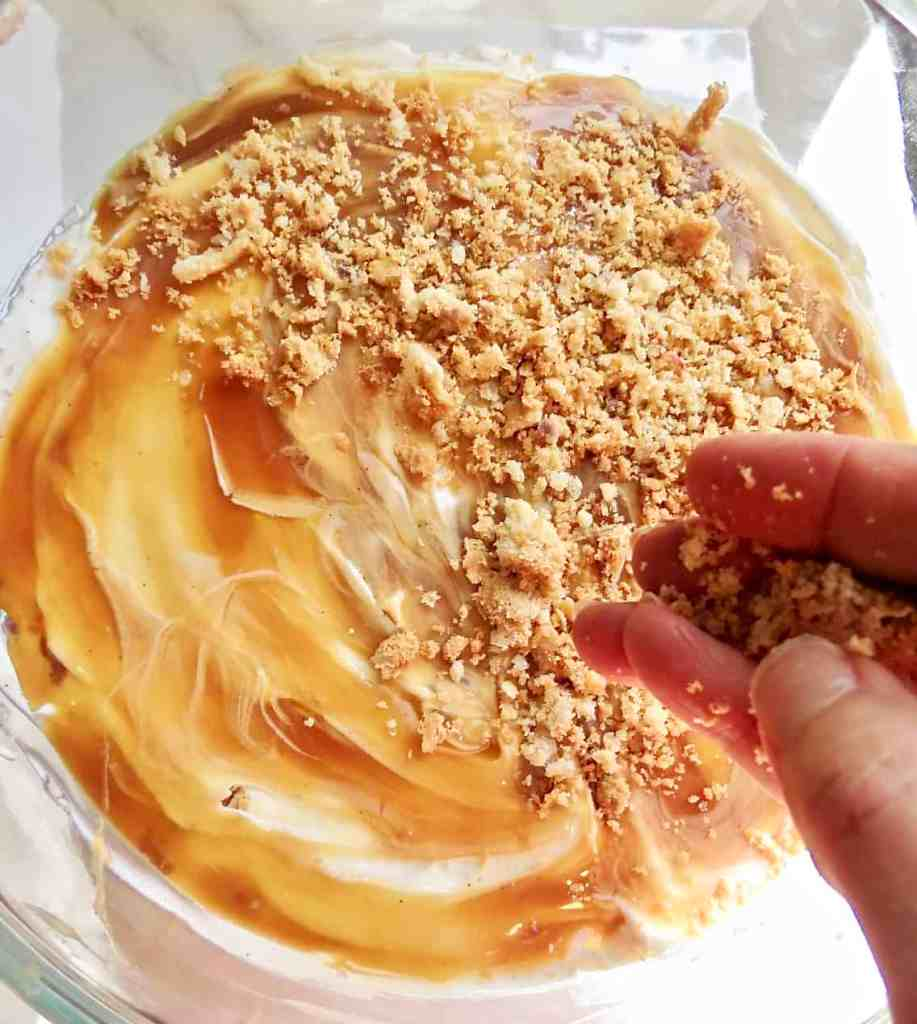 Sprinkling pie crust crumbs on top of caramel sauce for Easy Pie Trifle Dessert.