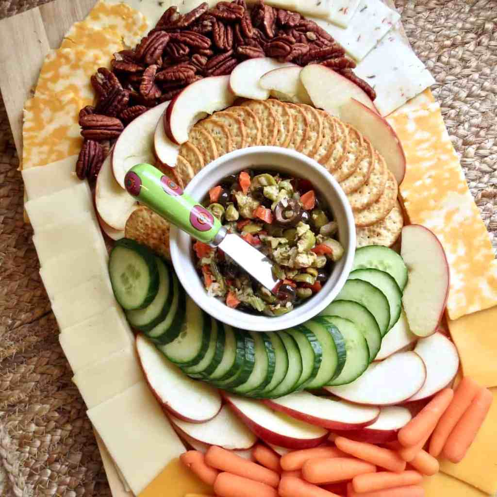 Sliced apples, pecans, crackers, sliced cucumber, baby carrots, and cheeses arranged in an oval around a bowl of olive salad on a cutting board for Easy Appetizers To Tease And Appease The Appetite.