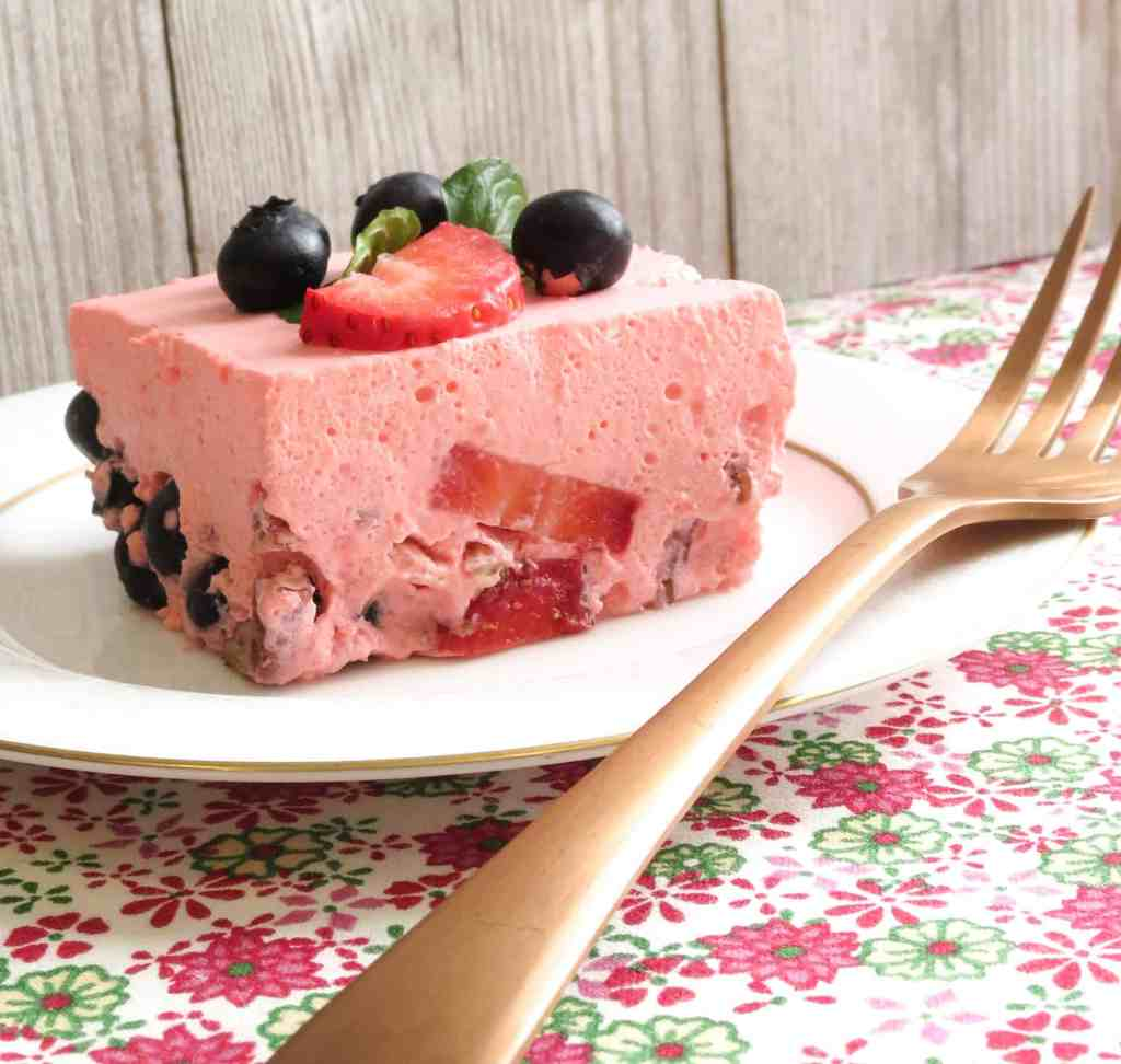 A white plate with a gold fork and a piece of Keto Strawberry Jello Dessert on it and berries on top.