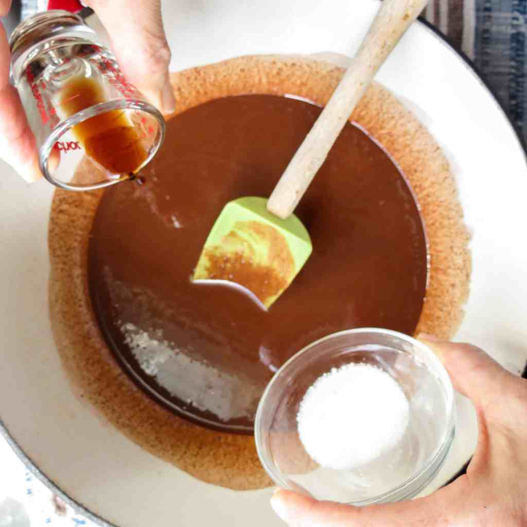 A white pot of melted chocolate with a green spoon in it and vanilla and stevia being poured in for Fat Bombs.