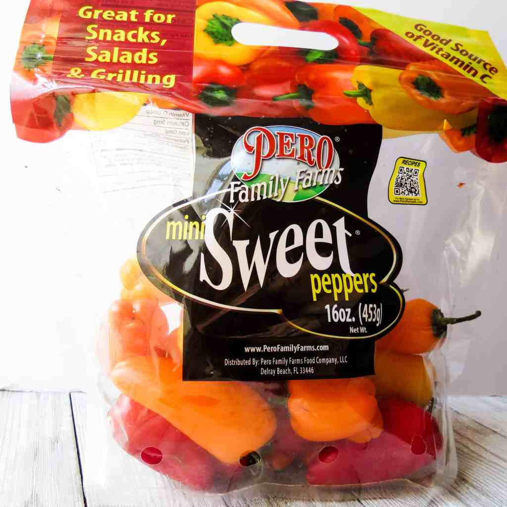 A bag of sweet red, orange, and yellow mini peppers.