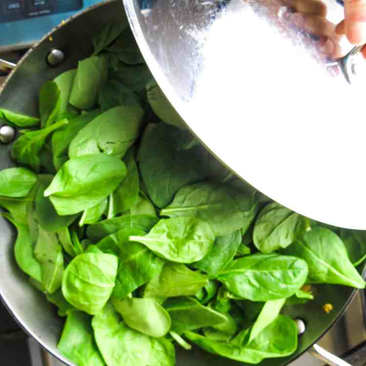 A pot of spinach with its lid being removed halfway over spinach.