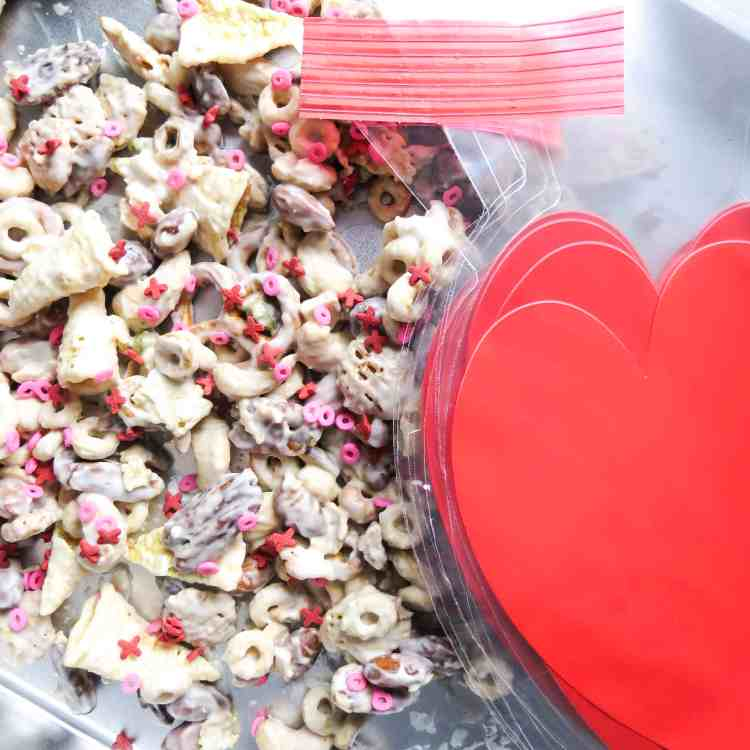 Candy spread out on an aluminum pan with heart plastic bags and ties.
