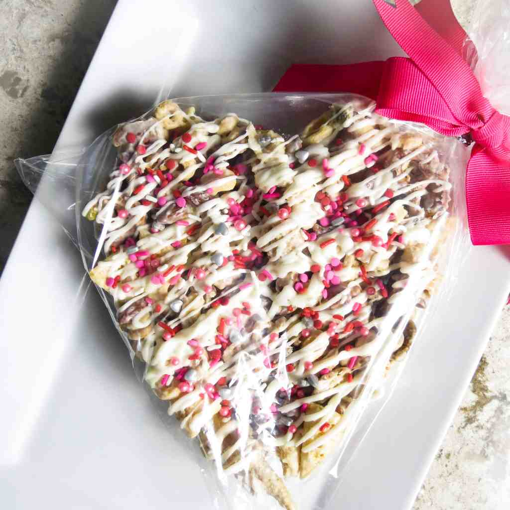Heart shaped Valentine Candy Crunch in a plastic bag and a pink bow.