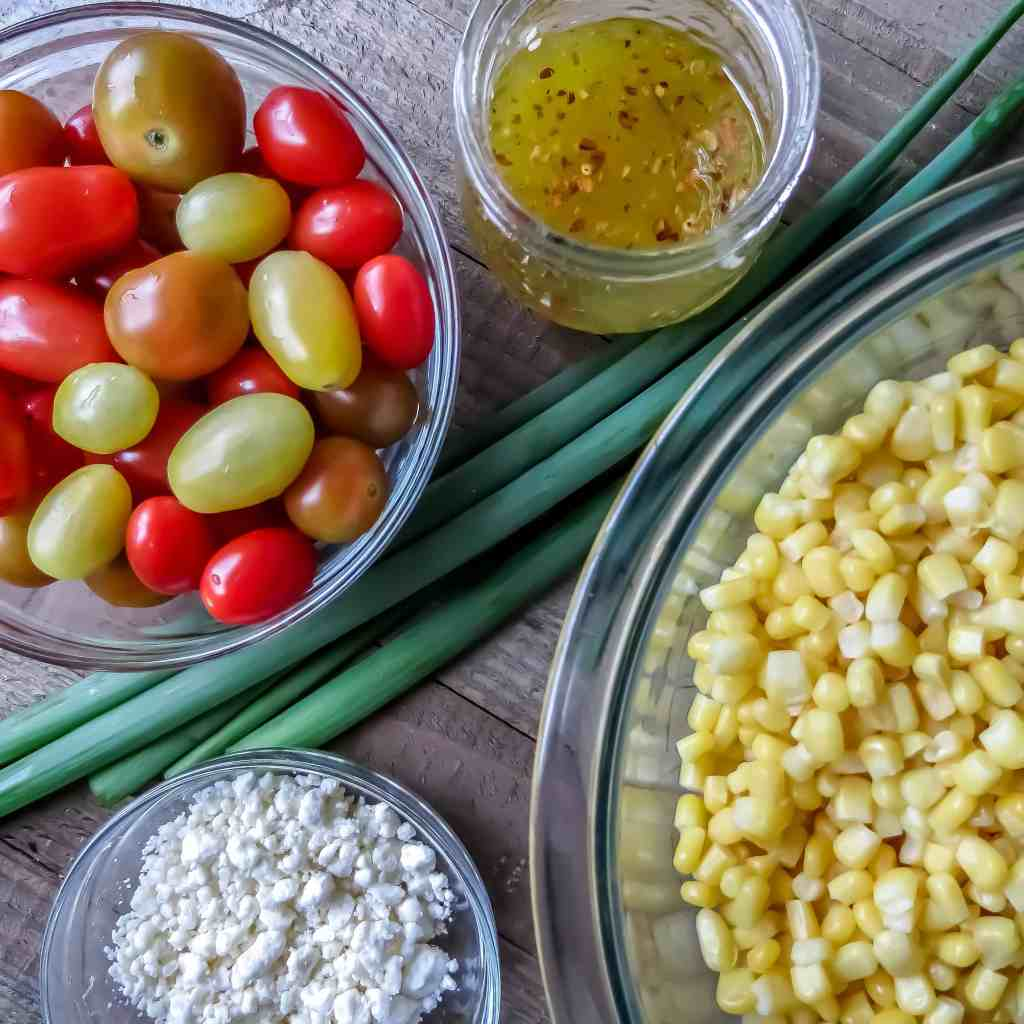 Individual bowls of corn, grape tomatoes, feta cheese, a jar of vinaigrette and some green onions on a wooden board for Corn Salad With Tomatoes.