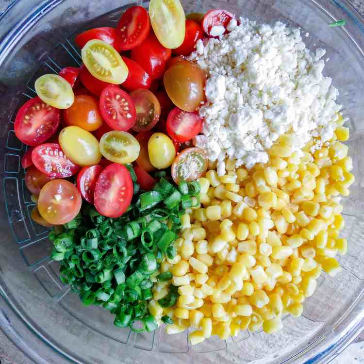 A glass bowl full of ingredients for Corn Salad With Tomatoes.