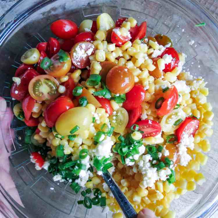 Glass bowl full of Corn Salad With Tomatoes stirred with a silver spoon.