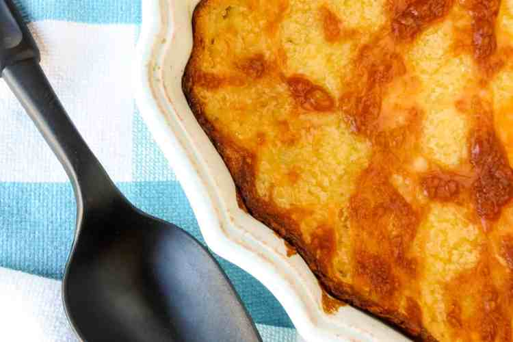 A casserole filled with Corn Casserole that has a browned topping of cheese with a black serving spoon on a blue and white towel.