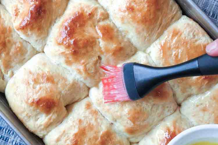 A pastry brush brushing melted butter onto a pan of baked Easy No-Knead Bread rolls.