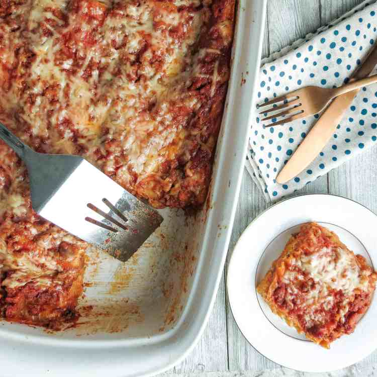 A white casserole dish of Easy Lasagna Recipe, Step-By-Step with a serving taken out and put on a white plate and a fork and knife on a blue and white napkin.