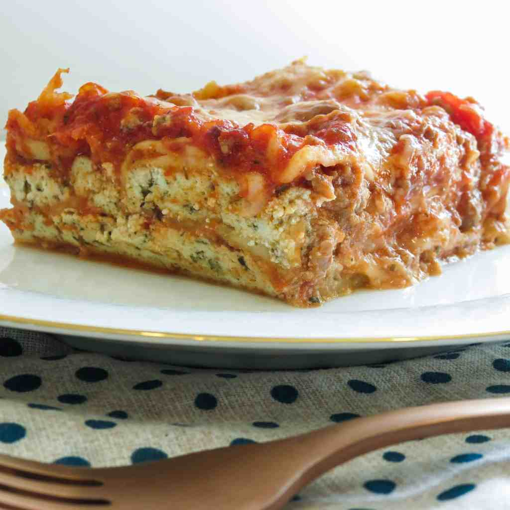 A serving of Easy Lasagna Recipe, Step-By-Step on a white plate on a blue and white napkin.
