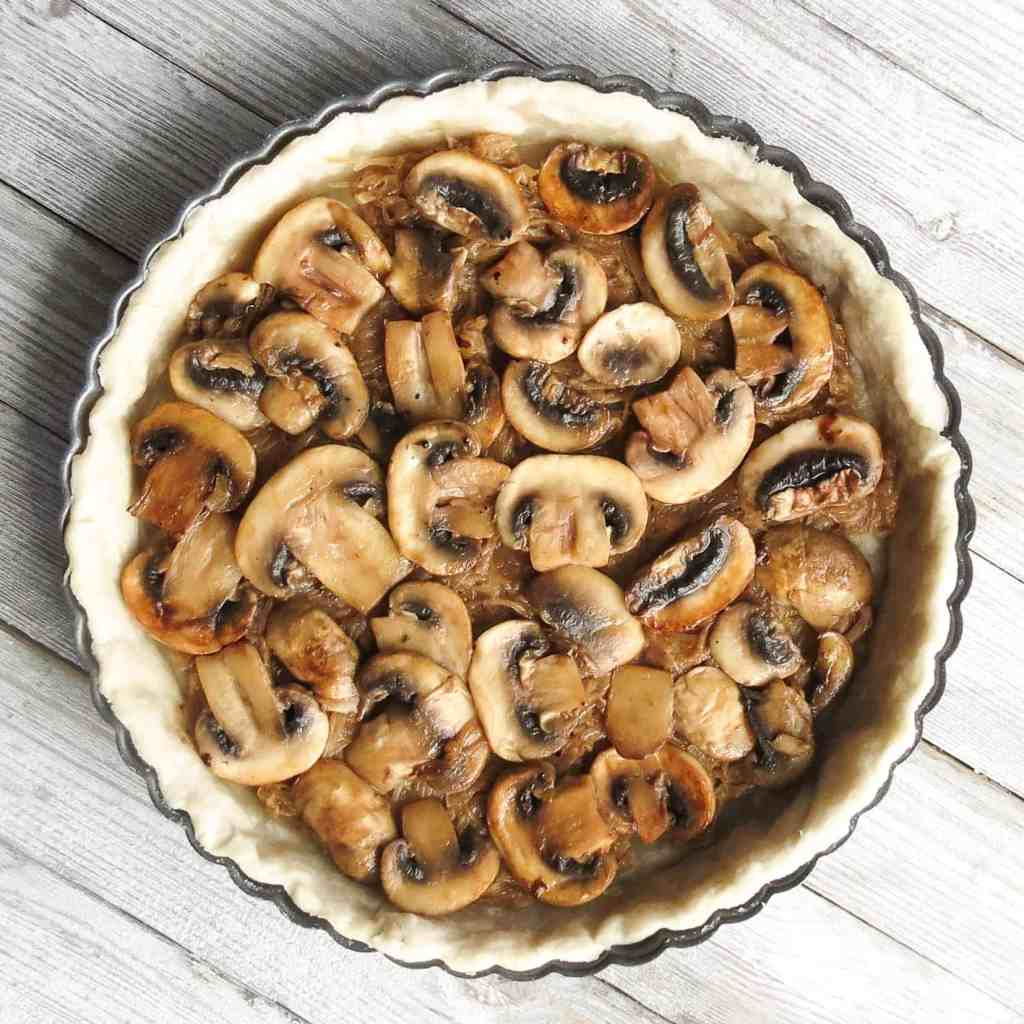 A tart shell filled with cooked mushrooms.