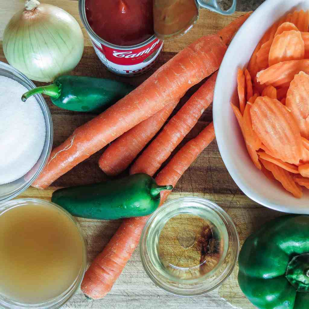 Carrots, onion, bell pepper, jalapeño pepper, and sauce ingredients on a wooden board for a salad.