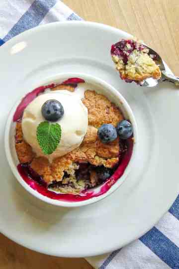 Easy Blueberry Pot Pie in a white ramekin bowl toped with ice cream next to a spoonful of pie.