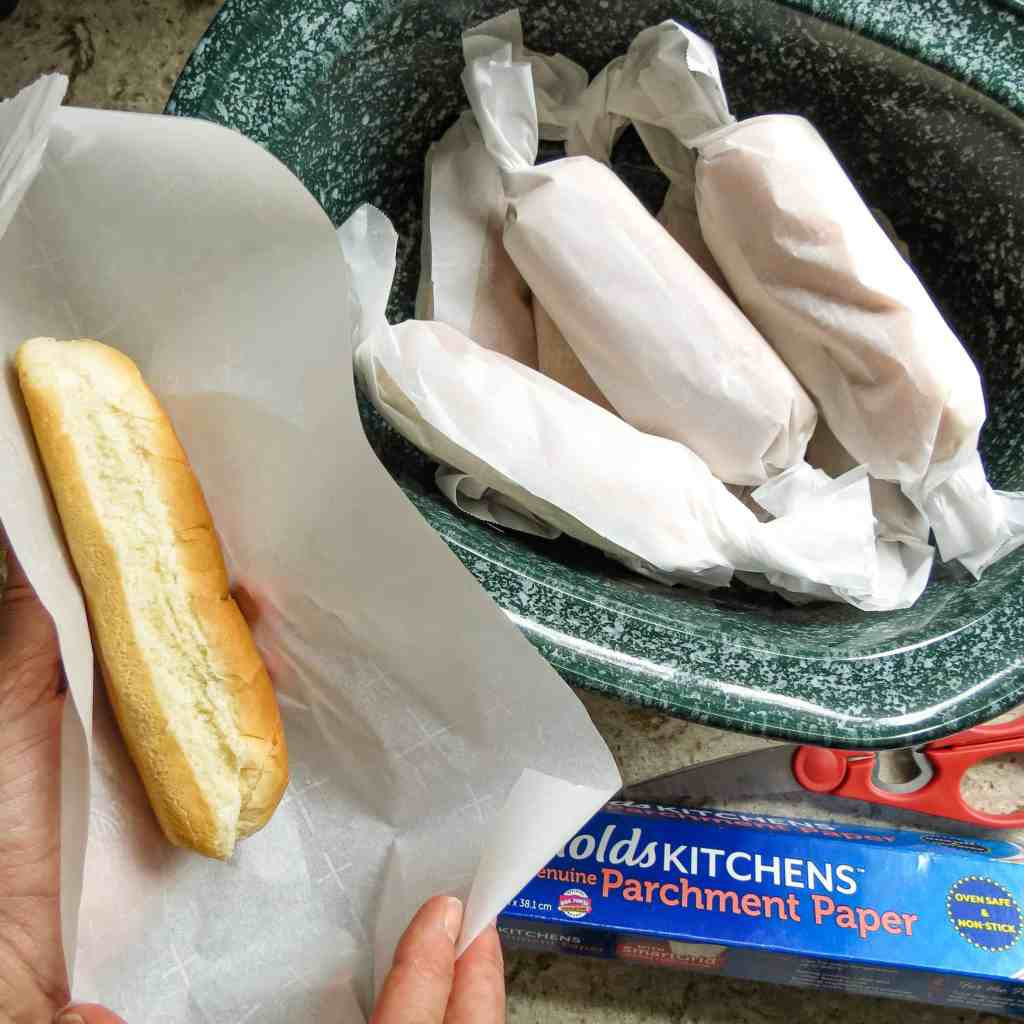 Buns wrapped in parchment paper stacked in a crock pot.