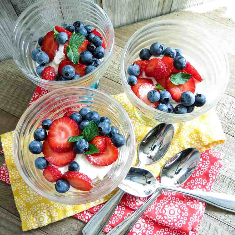Three glass dessert cups with strawberries and blue berries on top of cream filling for Keto Lemon Berry Dessert.