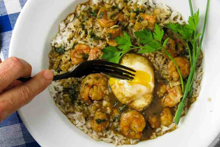 A white bowl of shrimp stew on rice with a poached eggs cut into with a fork.