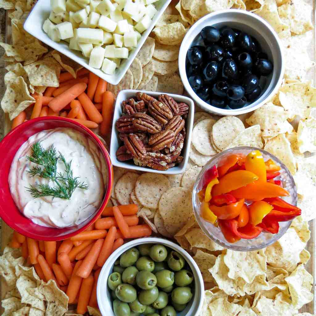 A board filled with white bowls filled with snacks with crackers surrounding them.