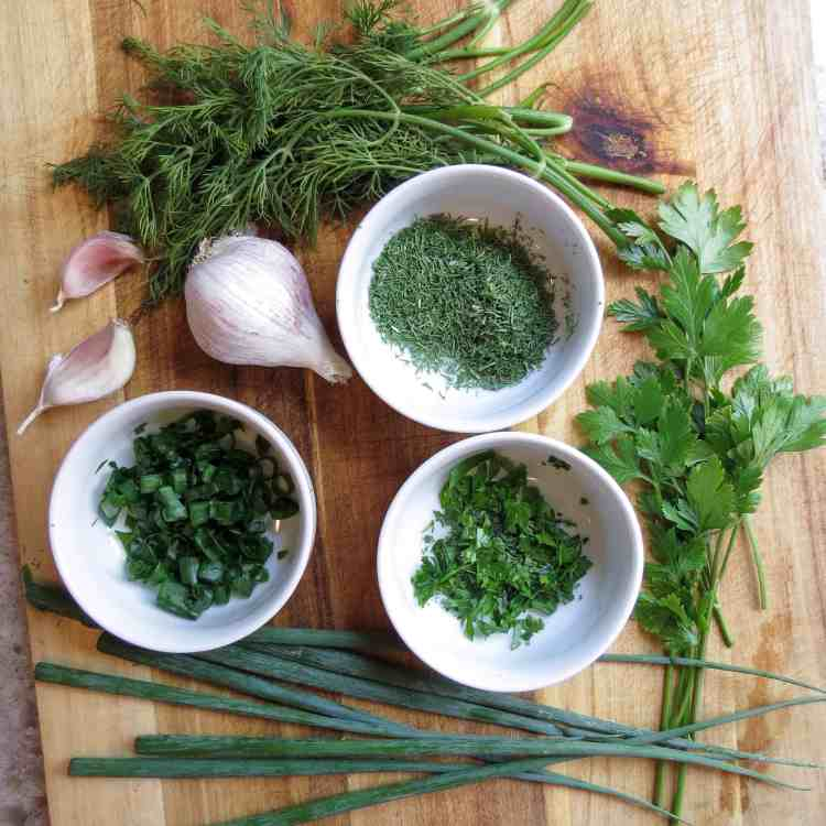 A wooden board with fresh herbs and a bulb of garlic.
