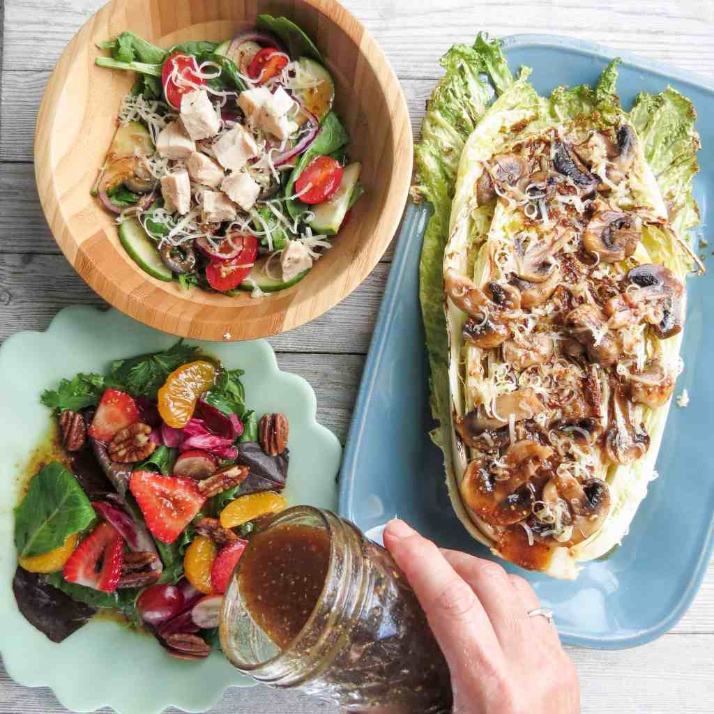 Dressing poured onto a fruit salad with a bowl of chicken salad and a plate of grilled greens and mushrooms.