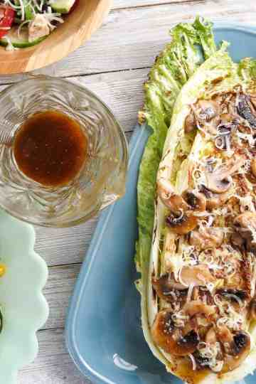 A plate of grilled greens and mushrooms with a dressing on a plank board.