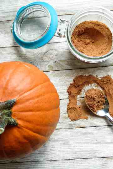 Jar of spice mix with a small pumpkin and a spoonful on a board.