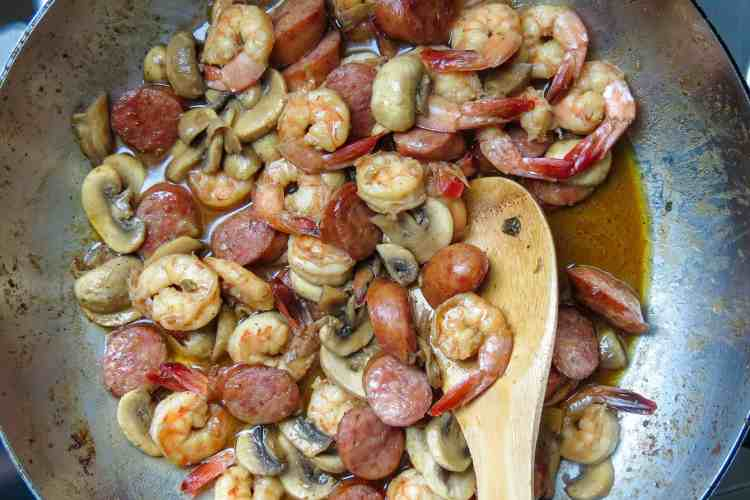 Cooked shrimp, sausage, and mushrooms in a spicy sauce in a pan stirred with a wooden spoon.