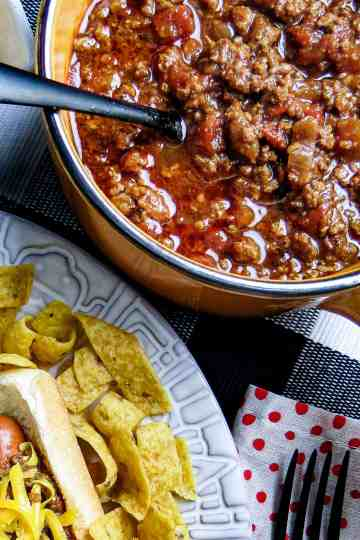 Chili in a pot next to a plate of chili dog and chips.