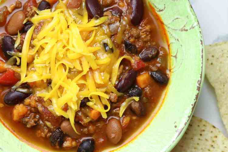 A bowl of chili topped with grated cheese.