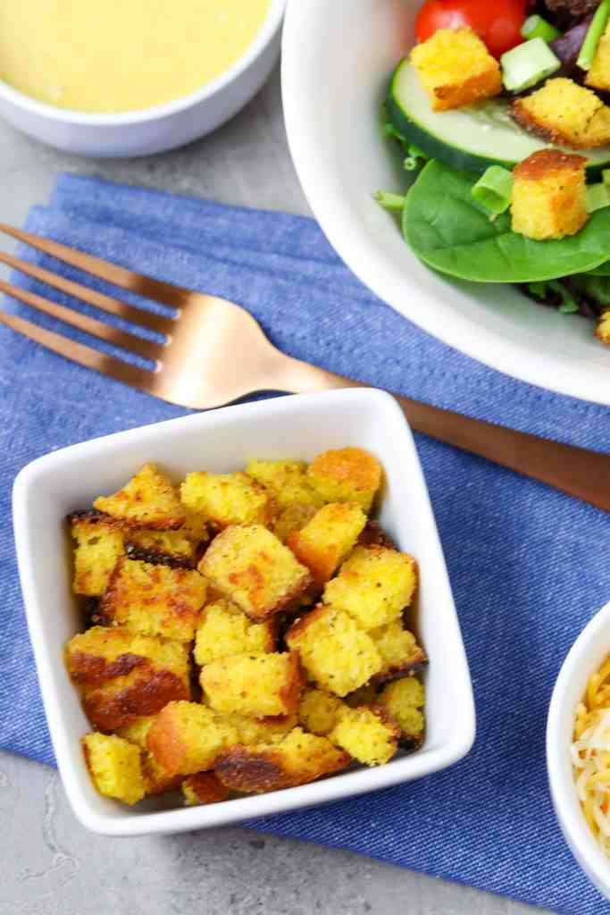 A bowl of cornbread croutons next to a salad.