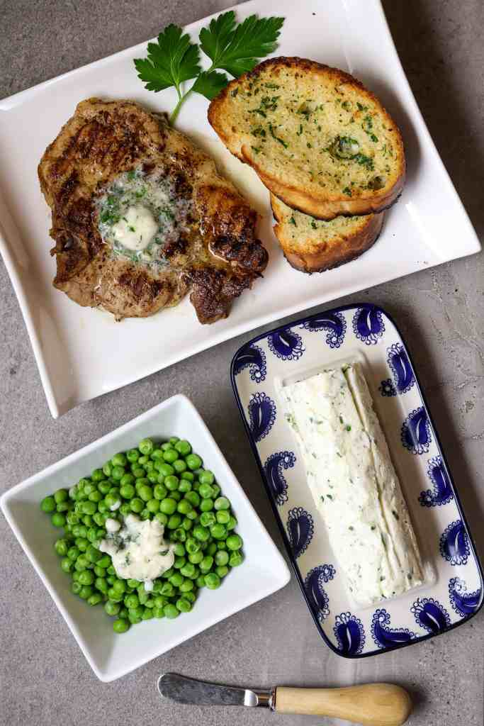 A log of Herb Butter with a plate of bread and a pork chop with a side of green peas.