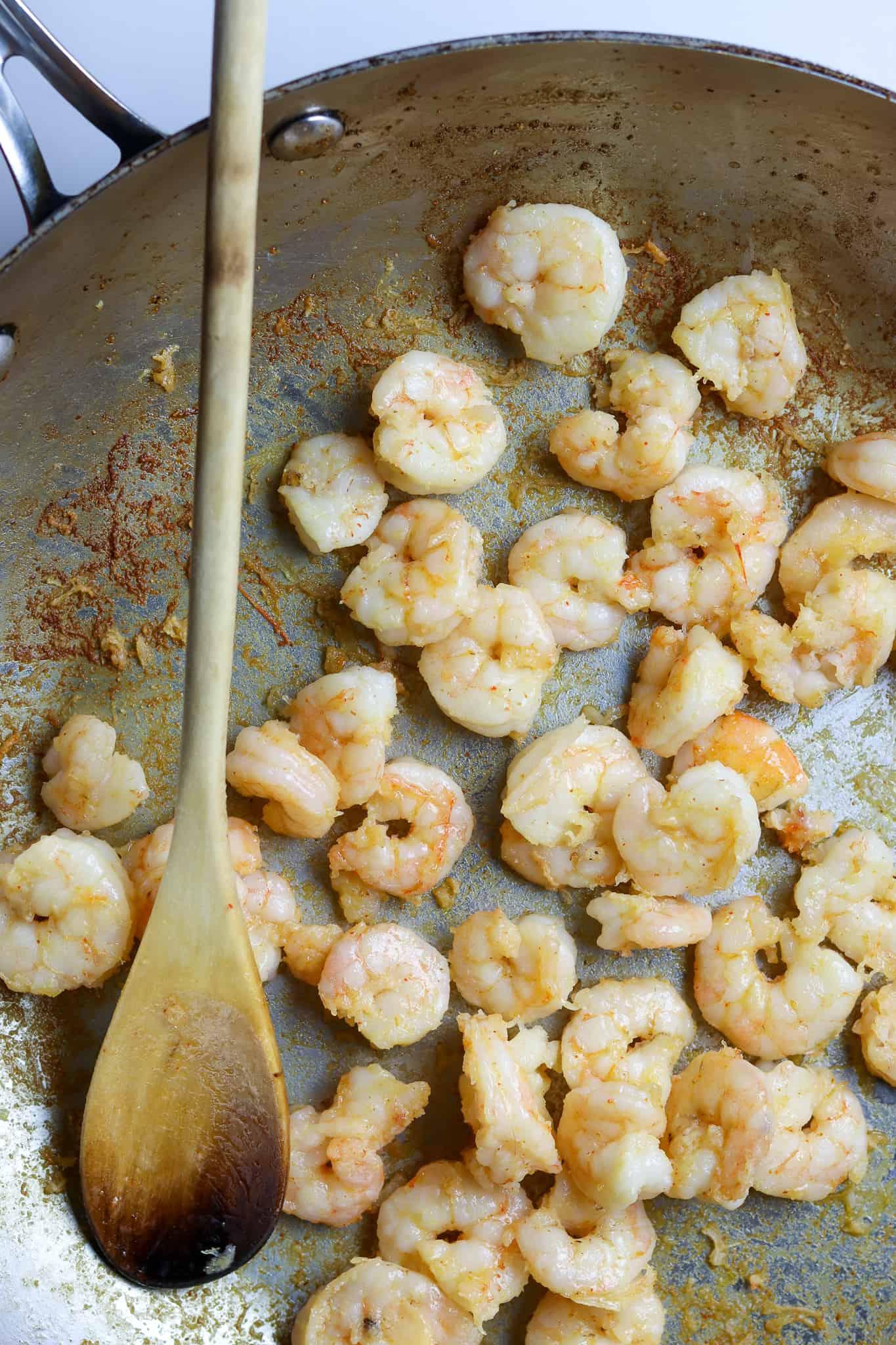 A pan of sautéed shrimp with a wooden spoon.