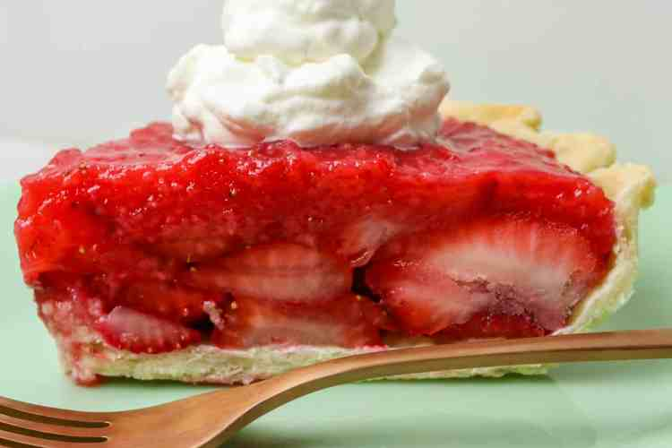Slice of strawberry pie with a dollop of whipped cream on top.
