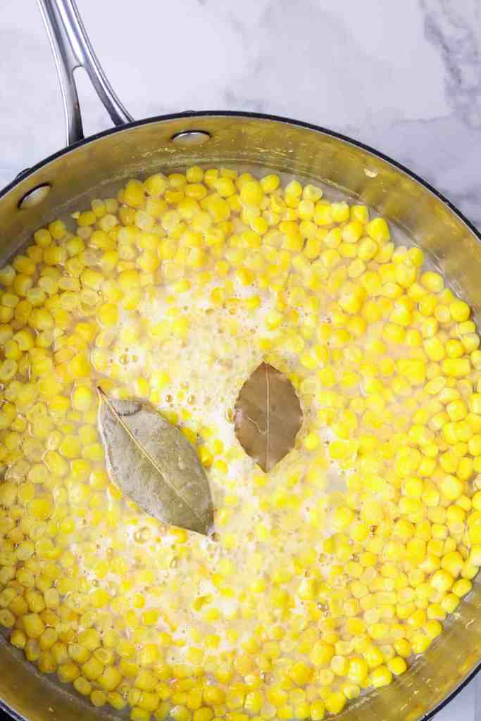 Corn cooking in a pan with bay leaves.