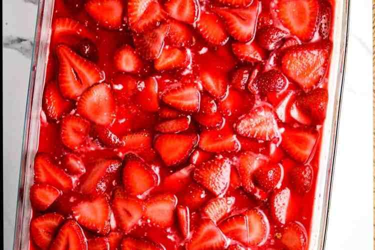 A glass casserole dish of strawberries and jello.