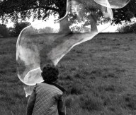 A closeup black and white photo of the back of a boy. A very large elongated bubble stretched out in front of him towards the top right corner of the image.
