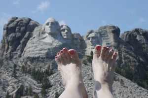 Lou Nell's bare feet w/pink toenails, Mt. Rushmore and blue sky in background
