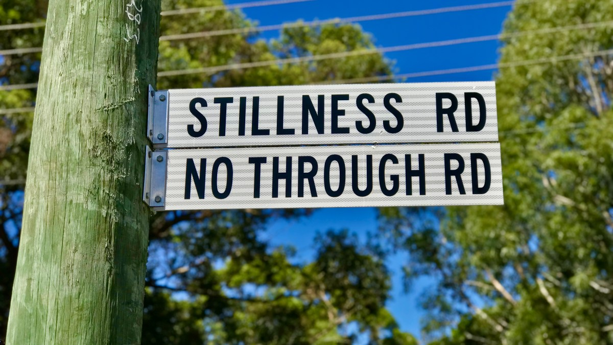 A street sign on a power pole that says 'Stillness Road, No Through Road'