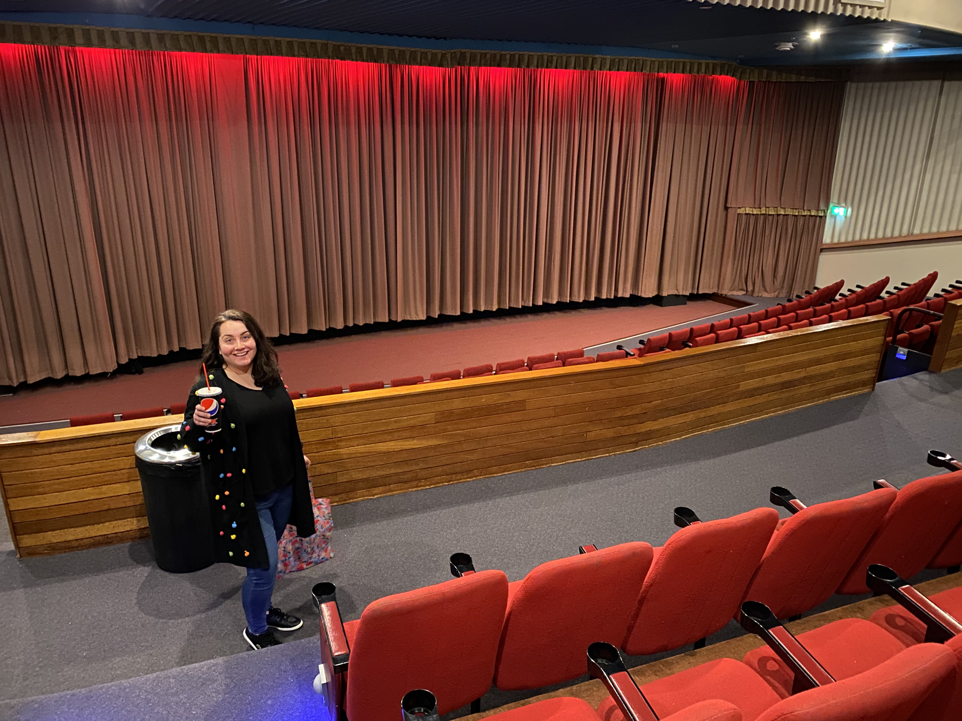 Natasha stands in an empty gala cinema with rows of red seats and the curtain drawn over the screen.