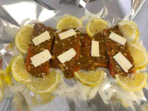 uncooked salmon with sauce, lemons, and onions
