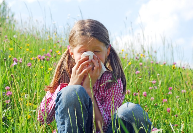 Girl sneezing in field