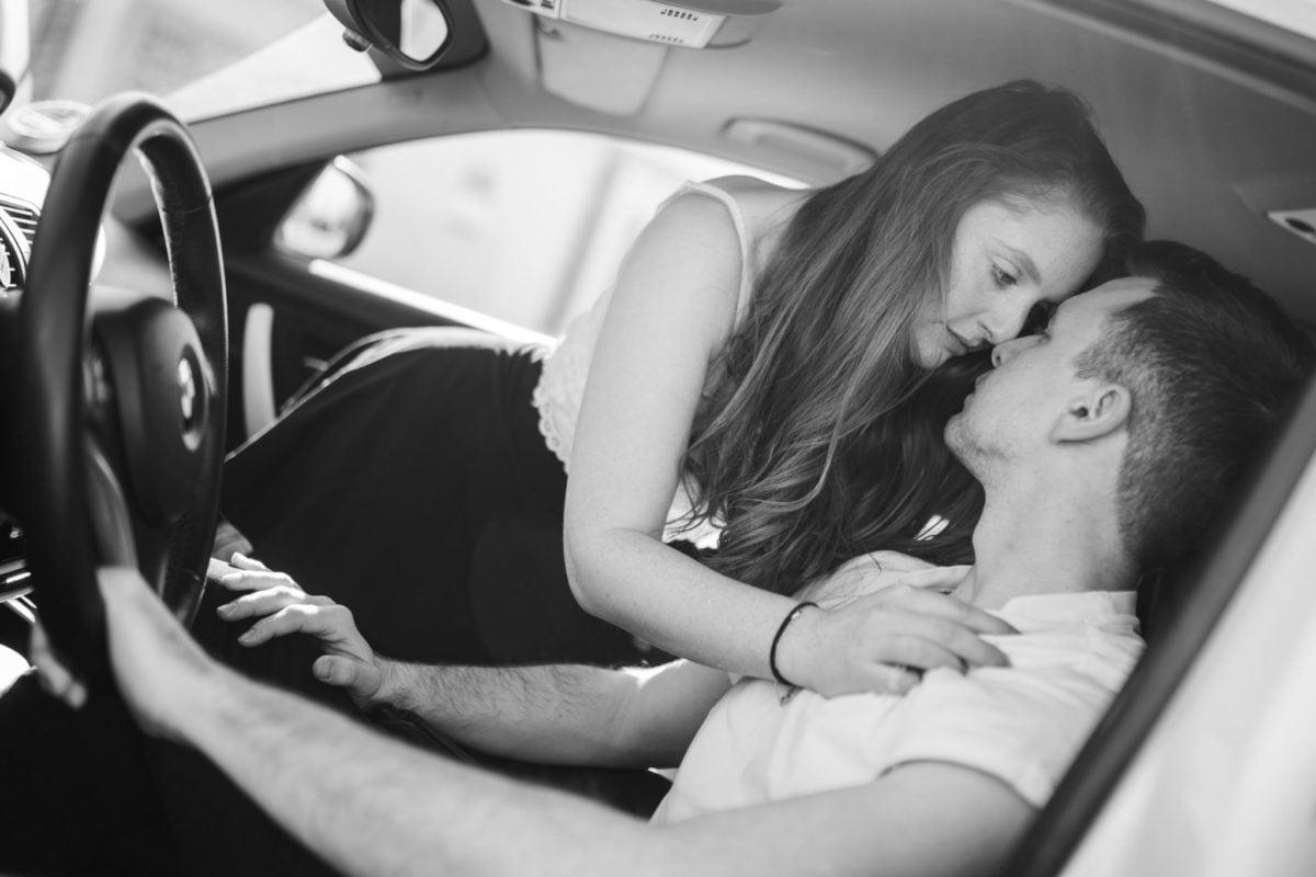 Er sitzt auf dem Fahrersitz, sie kniet auf dem Beifahrersitz und verführt ihn.
