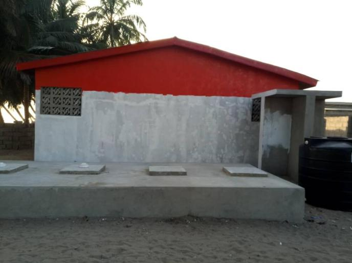 Back of Love Africa Project public communal washroom building painting with septic showing