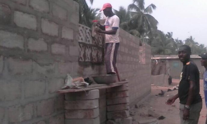 Bricklayer building window opening for 20-toilet public washroom to end open defecation in Saltpond, Ghana