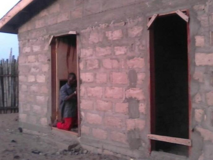 Carpenter installing door frame for Love Africa Project public washroom