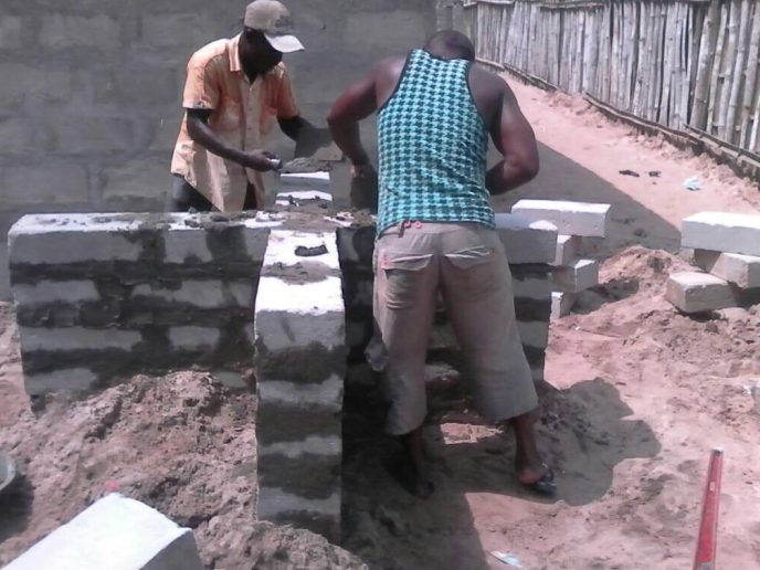 Masons building water tower for polytank for public washroom in Saltpond, Ghana