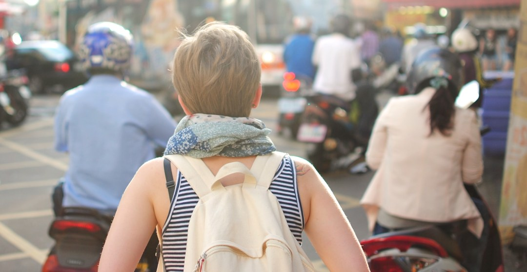 a traveling woman wearing a backpack shows that we are not here in this world to stay